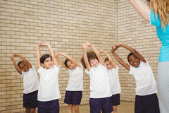 Teacher and students doing stretches Stock Image