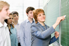 Teacher and students. Teacher and a group of students in the class Stock Images