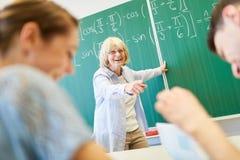 Teacher and students having fun in school. At math class stock photos