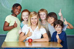 Teacher and students holding thumbs. Happy teacher and smiling elementary school students holding thumbs up Stock Photos