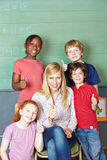 Teacher and students holding thumbs Royalty Free Stock Photography