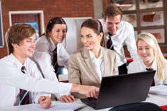 Teacher students laptop. High school teacher and students with laptop in classroom Stock Image
