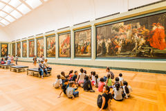 Teacher and students at the Louvre. A group of students with the teacher are viewing oil paintings in the Louvre museum royalty free stock image