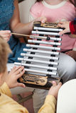 Teacher And Students Playing Xylophone In Class. Midsection of teacher and students playing xylophone in music class royalty free stock photos