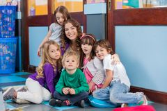 Teacher And Students Sitting Together On Floor. Portrait of happy young teacher and students sitting together on floor in kindergarten Royalty Free Stock Image