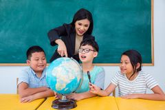 Teacher and students studying geography in class. Asian beautiful teacher and students studying geography in class Royalty Free Stock Photography