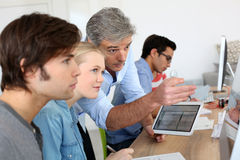 Teacher with students using electronical devices. Teacher using digital tablet in school class Stock Images