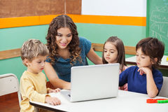Teacher And Students Using Laptop In Class. Beautiful teacher and students using laptop in class Royalty Free Stock Images
