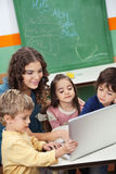 Teacher And Students Using Laptop In Class. Young teacher and students using laptop at desk in class Stock Photo