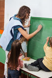 Teacher And Students Writing On Chalkboard In. Young teacher and students writing on green chalkboard in classroom Stock Photography