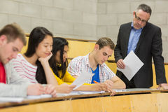 Teacher with students writing notes in lecture hall Royalty Free Stock Image