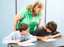 Teacher Supervises Testing. Teacher observes two school boys to make sure they aren't cheating on a test stock images