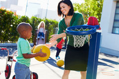 Teacher Supervising Breaktime At Elementary School Stock Images