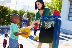 Teacher Supervising Breaktime At Elementary School Stock Images