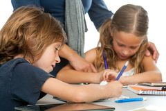 Teacher supervising kids homework. Royalty Free Stock Photos
