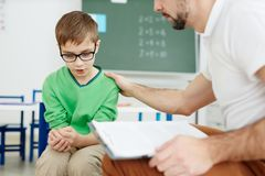 Comforting schoolboy. Teacher supporting upset or confused schoolboy during individual lesson stock images