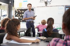 Teacher with tablet in front of elementary school class royalty free stock photography