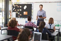 Teacher with tablet in front of elementary school class stock photography