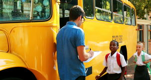 Teacher taking attendance while student entering in bus stock video footage