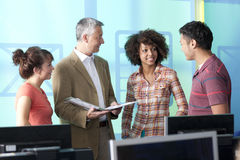 Teacher talking with students in computer lab stock image