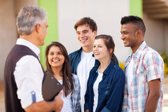 Teacher talking students. Middle aged high school teacher talking to students during break Stock Photo