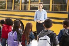 Teacher talking to elementary school kids by school bus stock images