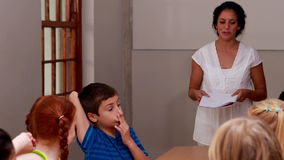 Teacher talking to her enthusiastic pupils. In elementary school stock video footage