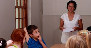 Teacher talking to her enthusiastic pupils. In elementary school stock video