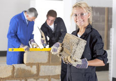 Teacher talking to student using level in bricklaying vocational school Royalty Free Stock Photography