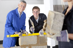 Teacher talking to student using level in bricklaying vocational school royalty free stock photos