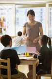 Teacher talking to students doing art in classroom Stock Photography