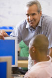 A teacher talks to a schoolboy using a computer Stock Image