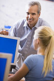 A teacher talks to a schoolgirl using a computer Royalty Free Stock Photo