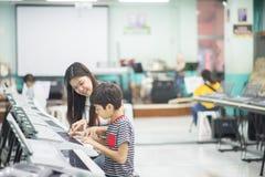 Teacher teach keyboard electone instument to a boy in the class room stock photos