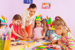 Teacher teach preschool kids in art class. Beautiful young teacher women show little children boys and girls how to make glue and draw craft image in preschool stock photo