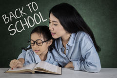 Teacher teaches a girl to read. Picture of a young teacher teaching a little girl to read a book in the class, shot with text of Back to School Stock Image