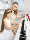 Teacher teaches little girl to play piano Stock Photography
