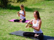 Young people meditating in yoga class in summer in nature. Teacher teaches the meditation of his students in yoga in a summer park. Sport, yoga, assanas concept Stock Photo