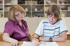 Teacher teaches a pupil at a table in the classroom.  stock photography