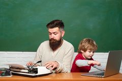 Teacher teaches a student to use a microscope. Education and learning people concept - little student boy and Teacher. Young boy doing his school homework with stock photo