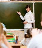 Teacher teaches students in classroom Royalty Free Stock Image