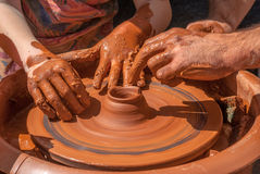 The teacher teaches to sculpt in clay pot on a turning pottery wheel Royalty Free Stock Photography