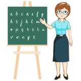 Teacher teaching alphabet on blackboard  Royalty Free Stock Images