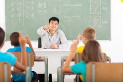 Teacher teaching chinese. Handsome young teacher teaching chinese language in elementary classroom stock photography