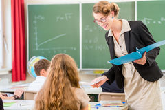 Teacher  teaching a class of  pupils in school. Teacher or docent or educator giving while lesson in front of a blackboard or board a sheet of paper and educate Stock Photo