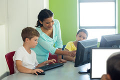 Teacher teaching computer to children Stock Image