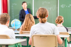 Teacher teaching or educate at the board a class in school. Teacher or educator or docent standing while lesson  in front of a blackboard and educate or teach Stock Image