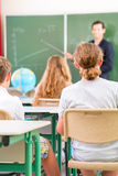 Teacher teaching or educate at the board a class in school. Teacher or educator or docent standing while lesson  in front of a blackboard and educate or teach Royalty Free Stock Images