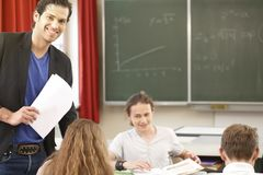Teacher teaching or educate at the board a class in school. Teacher standing while math lesson in front of a blackboard and educate or teach students or pupils Stock Photo