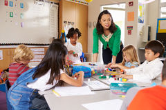 Teacher teaching elementary kids with block play in class Royalty Free Stock Image